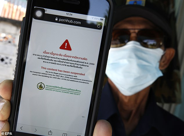 A Thai man shows the screen of a mobile phone after trying to access the adult website Pornhub, in Bangkok, Thailand today