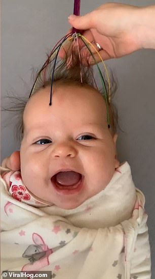 Baby Monica is enjoying every second of her head massage as she smiles and gurgles
