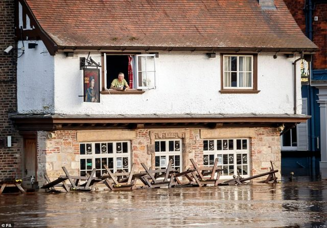 A man looks out of the window of the Kings Arms in York on Tuesday after the river Ouse burst its banks following heavy rain with flood warnings issued for locations across the country