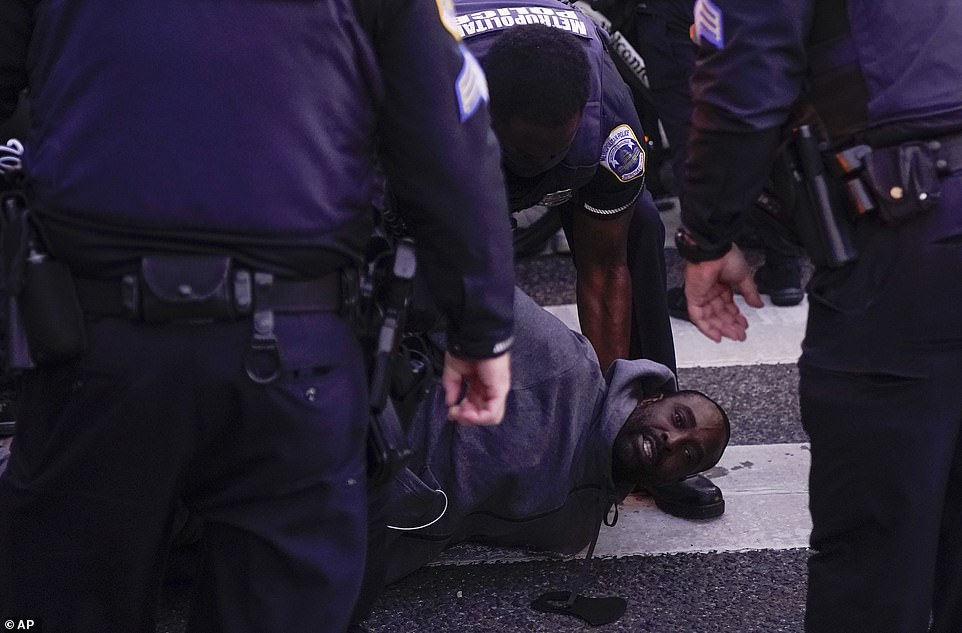 WASHINGTON DC:District of Columbia Metropolitan Police arrest a protester who was part of a group blocking police efforts to move an illegally parked truck out of the street at Black Lives Matter Plaza