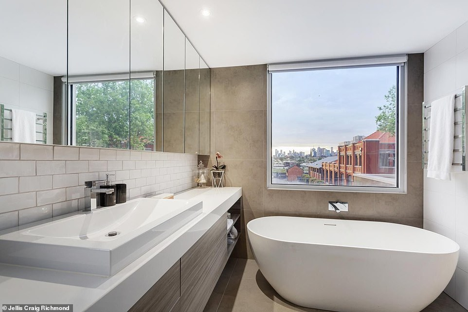 The beautifully renovated bathrooms also have 180-degree views of Melbourne's CBD, which can be seen here from the master