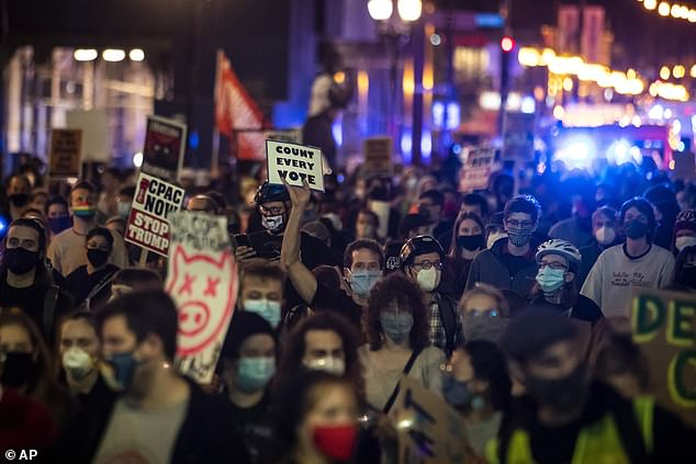Protesters march through the Loop to demand every vote be counted in the general election
