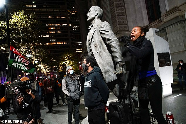 A demonstrator speaks as people gather after a rally demanding a fair count of the votes in Philadelphia, Pennsylvania