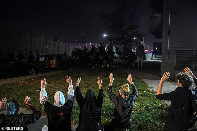 Protesters confront mounted police officers outside an apartment complex beside the Interstate 94 the day after Election Day in Minneapolis
