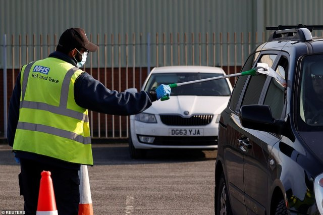 An NHS staff member uses a litter picker to give people their DIY coronavirus tests through their car window yesterday