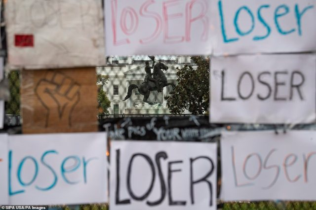 One section of the fence has seven posters that make up a rectangle with the word 'loser' written in different colors and different fonts as well as one sign with a drawing of the 'Black Power' fist