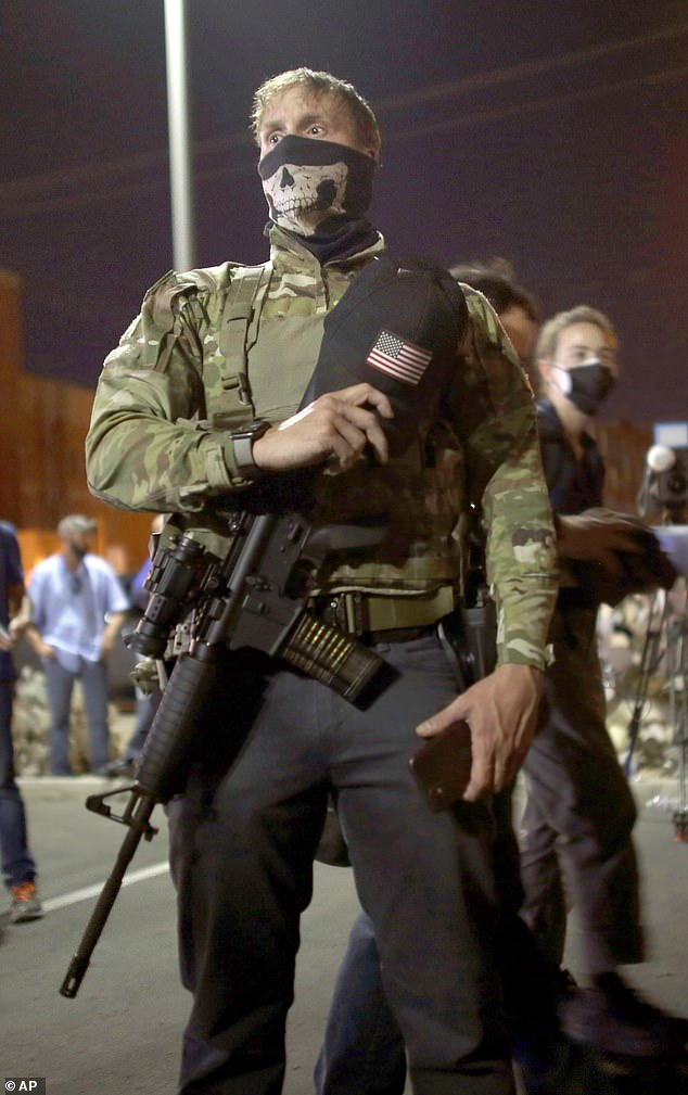 Some of the protesters, such as this man in Maricopa County in Phoenix, Arizona, pictured, attended the protests carrying firearms, including this AR-15 assault rifle