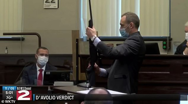 A prosecutor is seen holding the long gun, which the defense claimed Kerrilee used to commit suicide by shooting herself in the back of the head