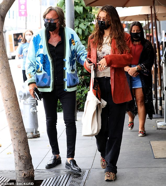 High and low: Bella managed to pair a more rumpled casual look with an eye-catching coral leather blazer as she walked up to the restaurant's outdoor seating area