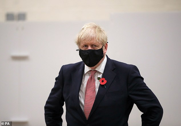 Boris Johnson, the first Prime Minister to cancel Remembrance Sunday, wore a poppy during a visit to a Covid testing centre at De Montfort University in Leicester yesterday