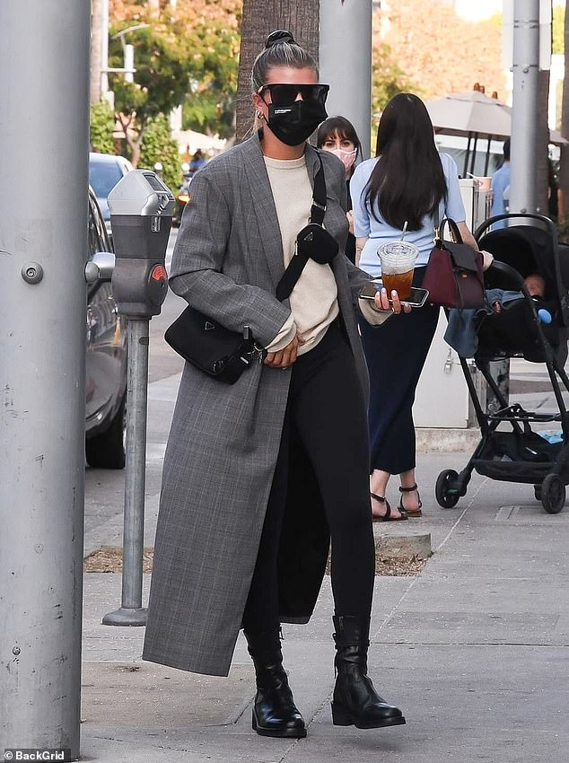 Chic:Sofia put on a chic display in a grey plaid longline coat that she layered over a beige crewneck sweatshirt