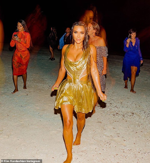 Birthday girl: Kim looked overjoyed as she danced about near the shore, and she seems to have gone in completely, as other photos show her emerging from the beach completely soaked