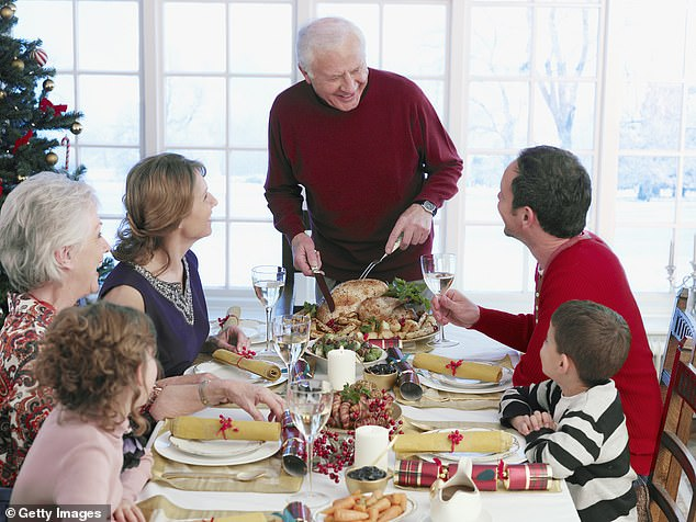Anyone spending time with family members from outside their own household at Christmas may be required to self-isolate for two weeks afterwards, newly released official documents suggest. Pictured: A family have a Christmas dinner (stock image)