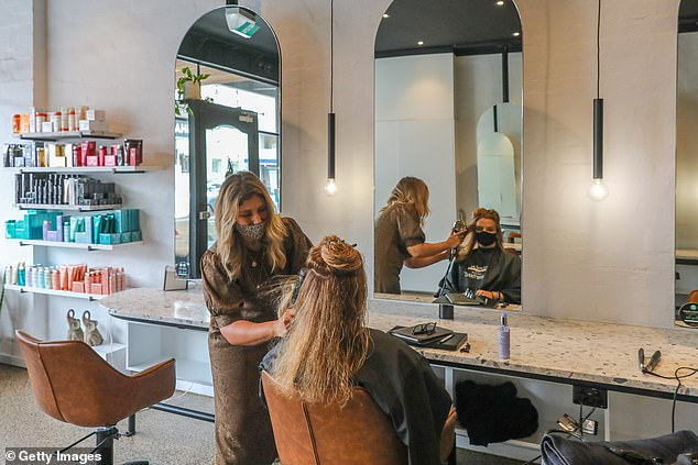 The RBA forecasts Australian wages on average will increase at a rate well below two per cent over the next few years (pictured, a hair stylist in Melbourne gets back to work on October 19)