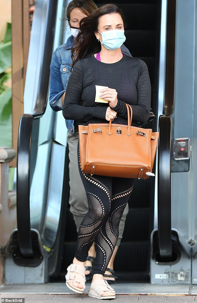 Birkin babe: She wore a surgical face mask and finished the look with some beige Birkenstock sandals, while carrying a cognac leather Hermès Birkin bag