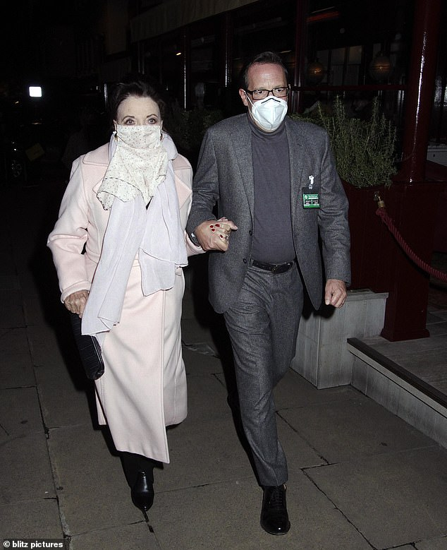 Chic: Joan Collins looked effortlessly elegant as she headed out for dinner at LouLou's Restaurant in London's Mayfair with her husband Percy Gibson on Wednesday evening