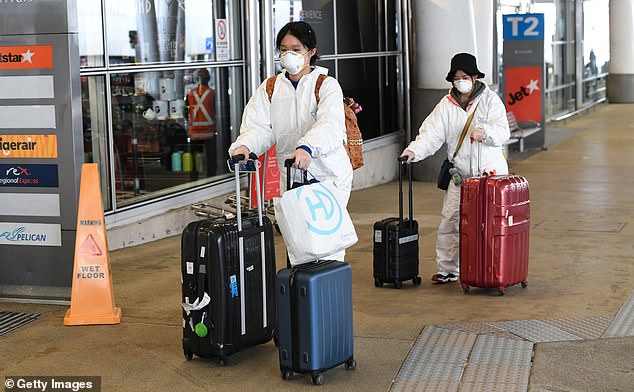 Two women wearing face masks and protective suits walk their luggage to a taxi rank at Sydney Airport on August 5