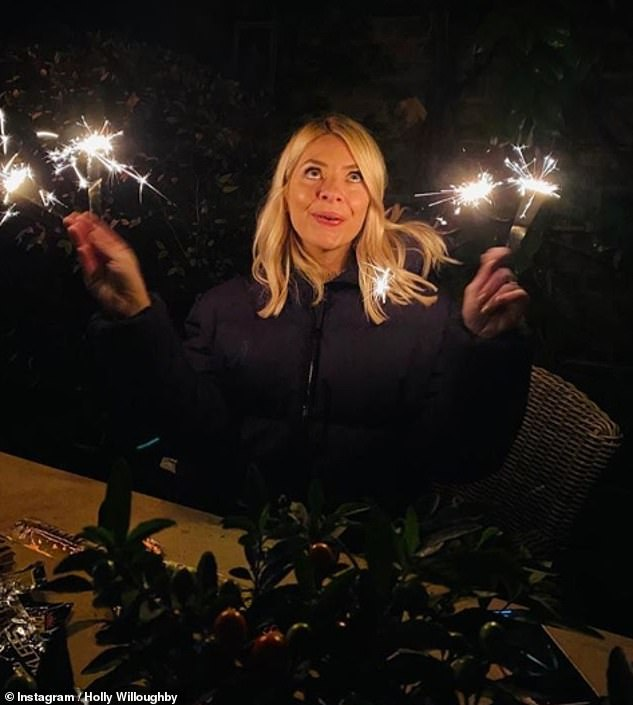 Fun: Holly was among the stars celebrating Bonfire Night in a low-key fashion on Thursday as the UK entered its second lockdown