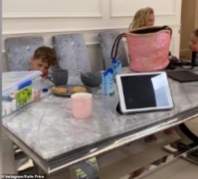 Playing games: In the video, Katie's six-year-old son Jett can be seen playing Minecraft while his sisters put on makeup next to him