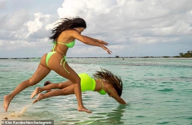 Take the plunge: Kim shared more photos of herself diving into the revealing green suit, including with her sister Kourtney and friend La La Anthony