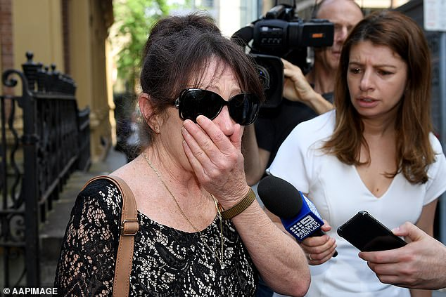 Lindy Anderson, the mother of Liam Anderson, covers her face as she leaves the Supreme Court in Sydney following the verdict on Thursday