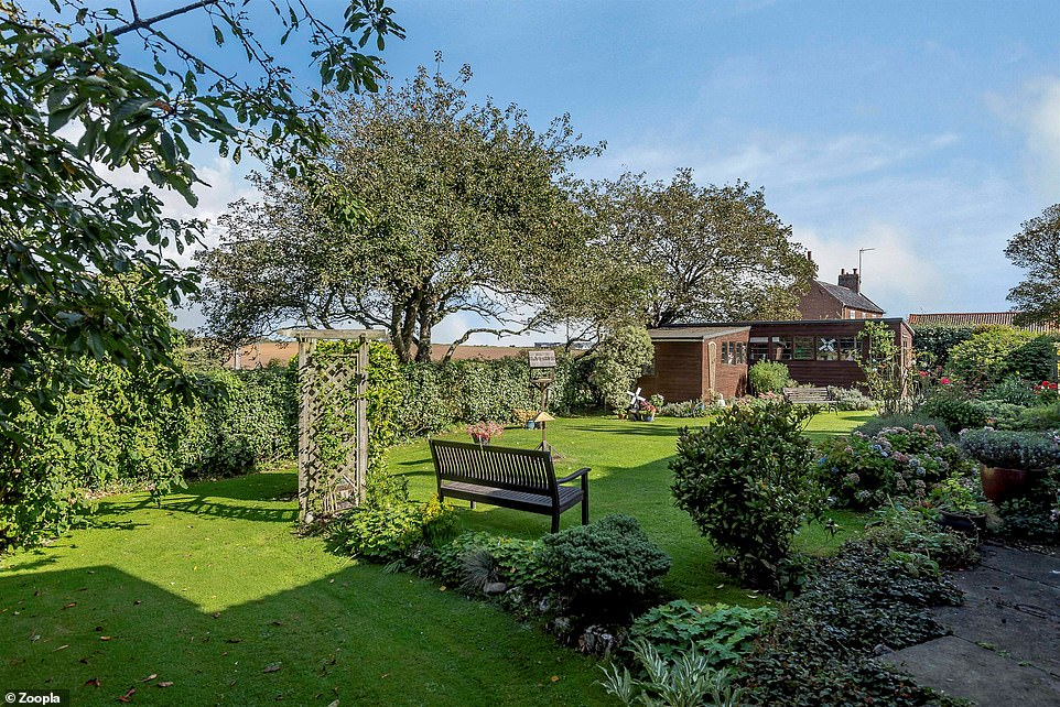 The cottage enjoys an enclosed garden with a lawn area and a timber workshop