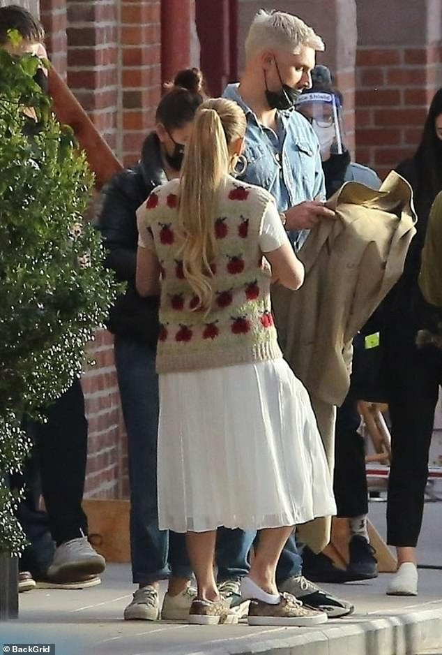 Apples to apples:For her third and final look, Lopez threw on a beige trench coat and an adorable wool vest that looked to be covered in images of apples