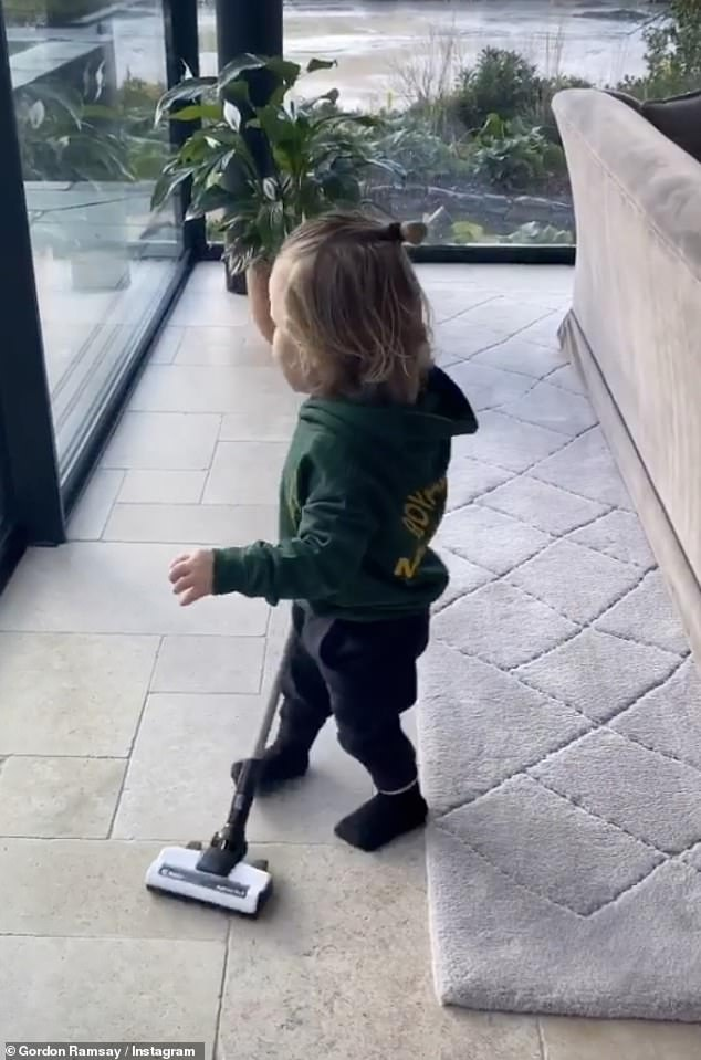 Domestic duties:Oscar looked adorable as he trotted around the stunning house in a mini green Royal Marines hoody, in a video captioned 'Dusting Down' by his famous dad