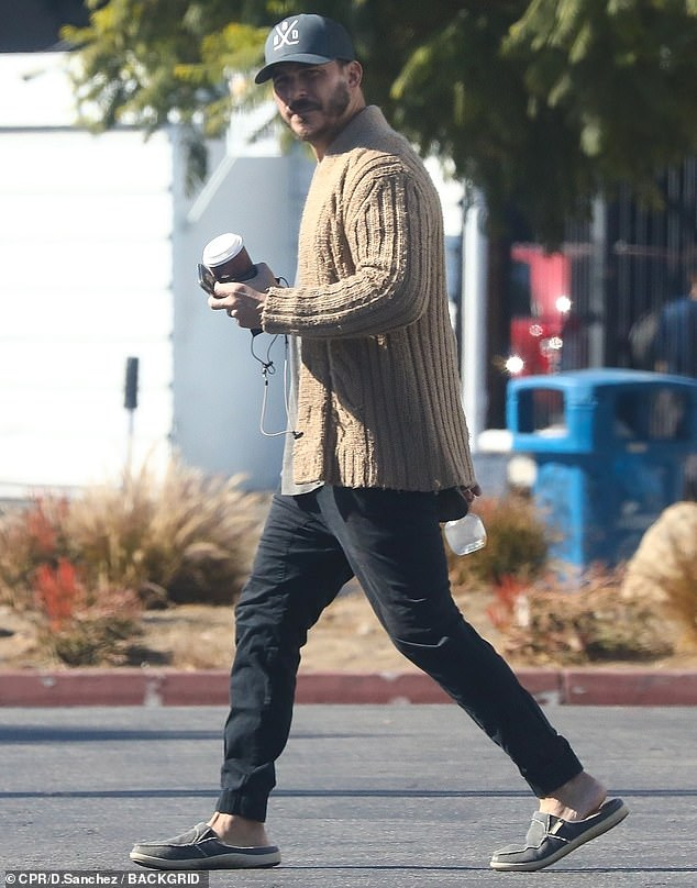 Staying warm: Jax, 41, also favored a sweater in the form of a fuzzy tan cable knit cardigan left unbuttoned over his gray T-shirt