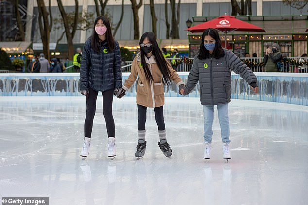 Women wearing masks hold hands while skiing in