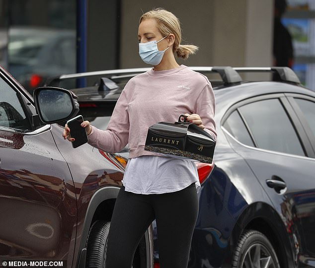 Effortless style: Carrie teamed a white top with a pink sweater and black full-length leggings. She was spotted heading back to her car with a cake box from Laurent French Artisan Bakery