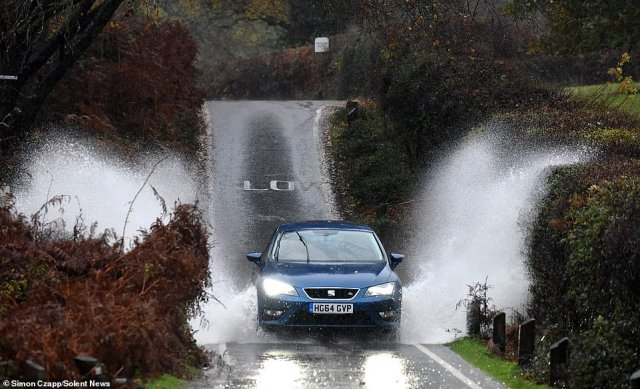 The MET Office has issued yellow weather warnings in the south of England and across Northern Ireland as both areas are set to be hit with torrential rain and winds. Pictured: Cars driving through floodwater in Cadnam near Southampton