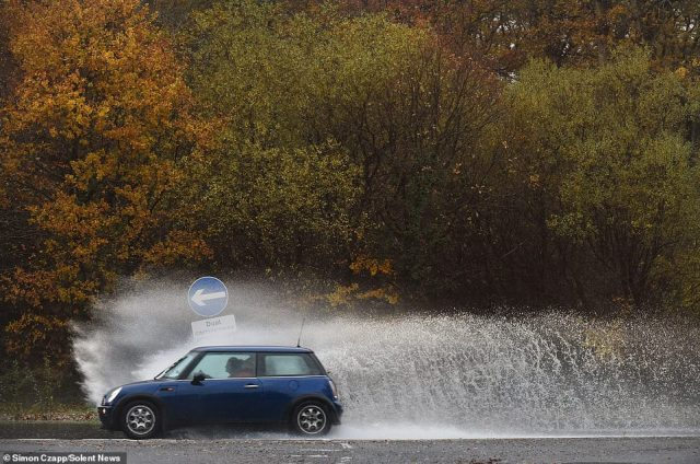 Roads turn to rivers after persistent rain on Saturday and with this morning continuing much the same. Pictured: Cars drive through Cadnam