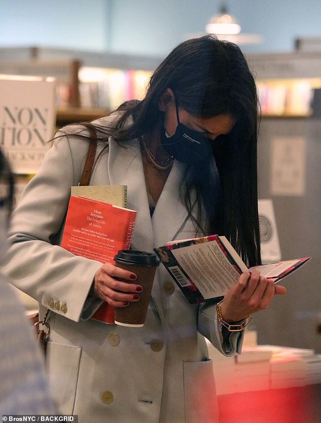 Choices choices: The Ohio-born 41-year-old perused one book while carrying Elena Ferrante's The Lying Life of Adults and Paulo Coelho's The Archer