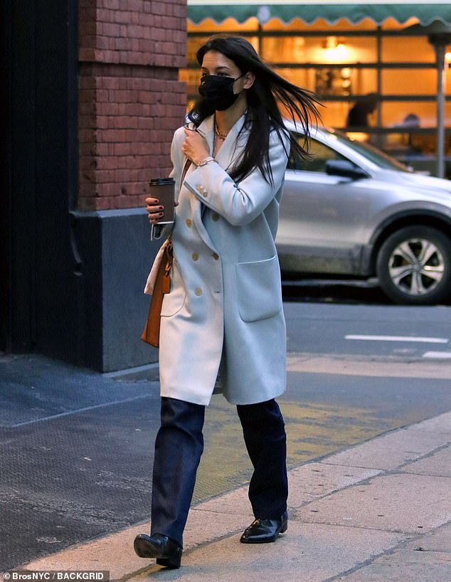 Caffeine fix: Holmes bundled up in a beige double-breasted winter coat over black slacks and patent leather shoes and she toted a brown bag