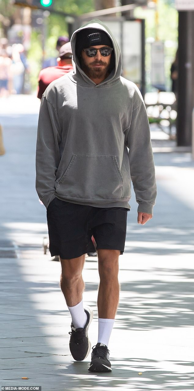 Zac Efron goes incognito by wearing a hoodie and sunglasses while shoe shopping in Adelaide