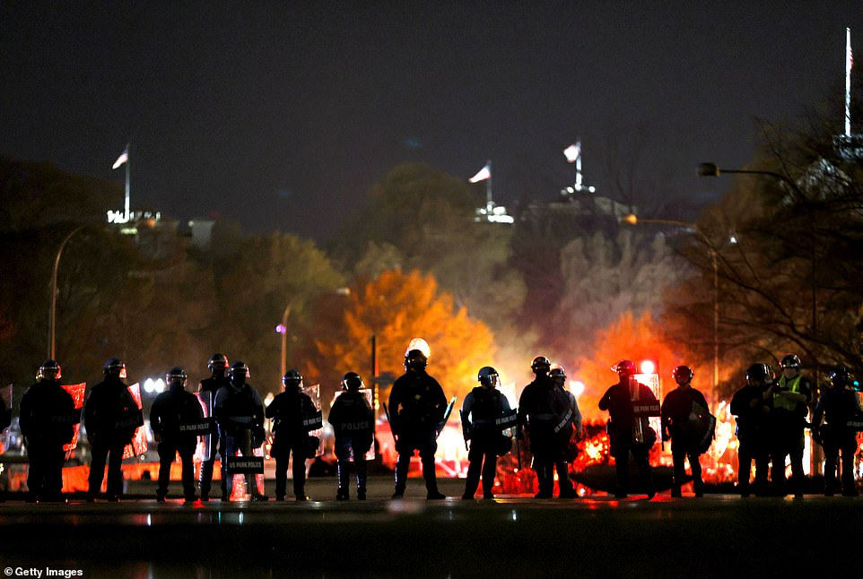 Police officers stand in line as they monitor a protest following the 'Million MAGA March' as tensions rose between Trump supporters and those protesting against him. At least twenty people were arrested as of 10pm Saturday