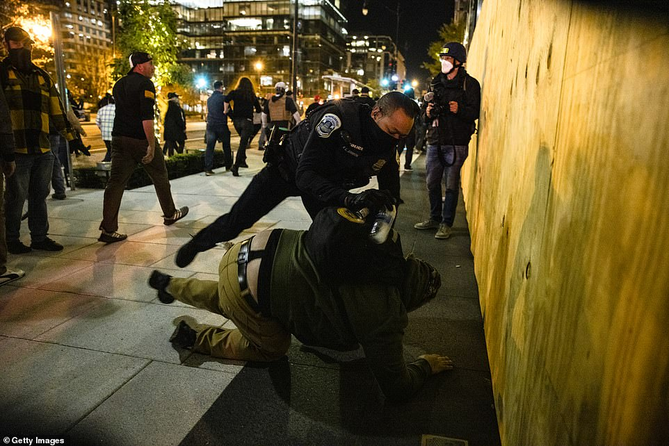 A police officer arrests a member of the Proud Boys during clashes with an Antifa member in the middle of the street
