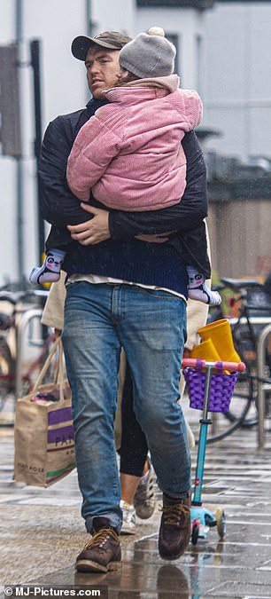 Doting: Max have India a piggyback before cradling her as the family walked down the street