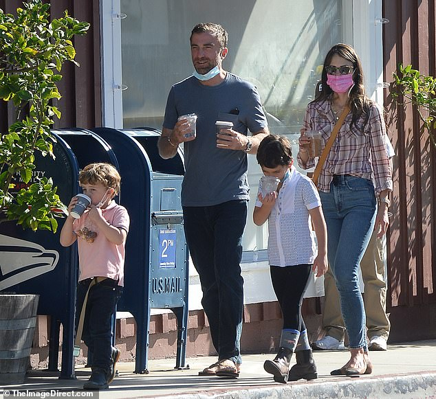 Relaxed: The foursome were seen holding beverages to go. The actress was casually stylish in a check shirt and blue jeans, and she kept a pink face mask in place as she walked along