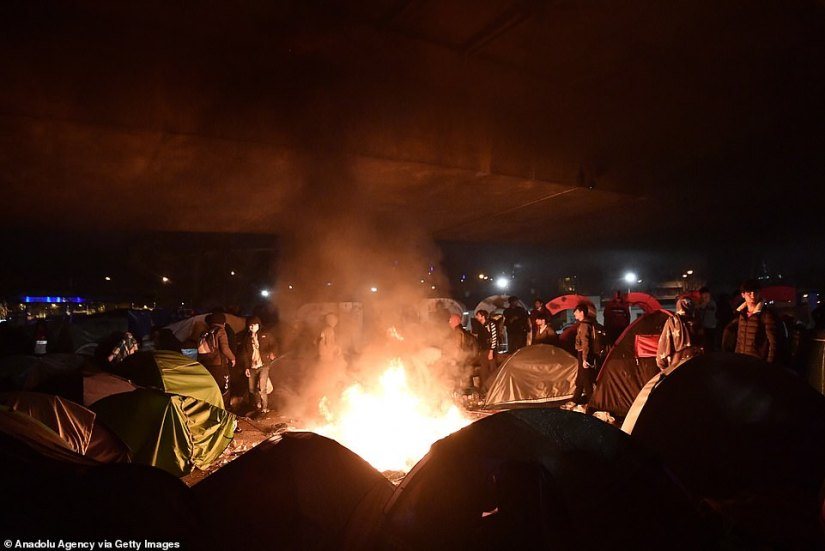 Migrants start a bonfire in the middle of their camp last night which rapidly spread out of control and sent smoke billowing over the motorway above