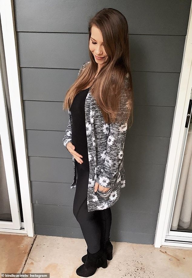 Baby on board: In August, Bindi revealed her pregnancy, uploading a photo to Instagram of herself and Chandler holding a tiny version of the Australia Zoo uniform