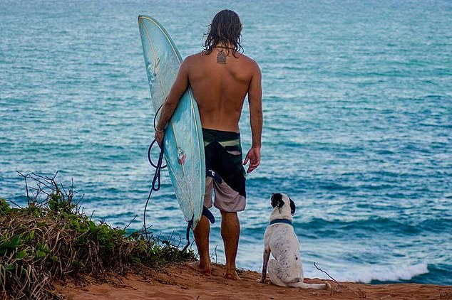 Mr. Pereira enjoys the waves with the dog of the Brisa family