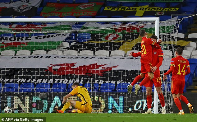 Finland goalkeeper Lukas Hradecky (L) reacts as Moore is congratulated by his team-mates