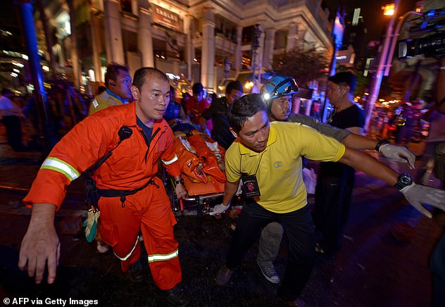 Emergency: While on their way to a nearby restaurant on August 17, Jimmy and Jane noticed a large crowd gathered in front of the shrine and roadworks surrounding the area. Pictured: Thai rescue workers carry one of the 125 people injured after the pipe bomb exploded
