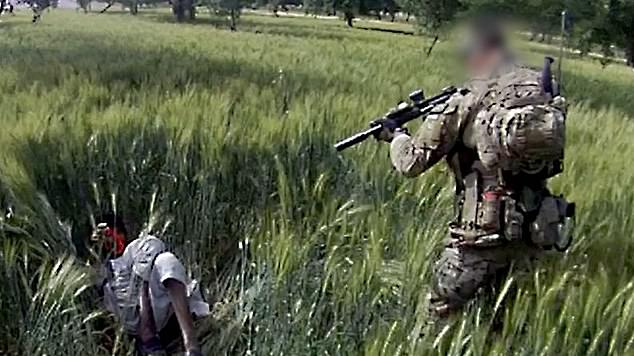 One video (pictured) shows an Australian soldier opening fire on a man as he cowers in a field at the village of Deh Jawz-e Hasanza in Afghanistan and is under investigation