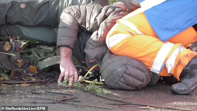 Footage shows the worker with his knee on the neck of the hooded man, whose head is pinned against the floor, during the incident at the site in Fradley, Staffordshire