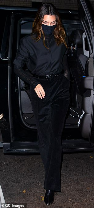 Wear a mask: Jenner finished the ensemble with a black face mask and a pair of black leather stilettos booties