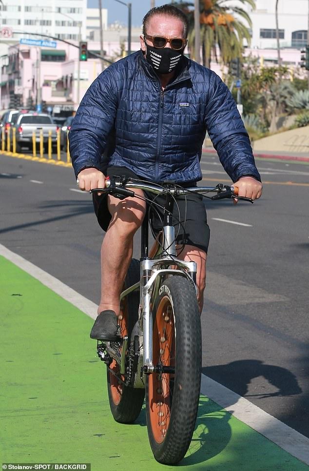 Arnold Schwarzenegger bundles up in a puffy blue jacket as he goes for a bike ride in Santa Monica