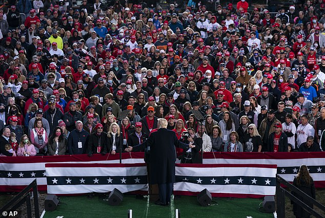 Trump is seen at a rally in Ohio on October 24, where most people in the crowd are not wearing face masks and not following coronavirus social distancing rules meant to stop its spread